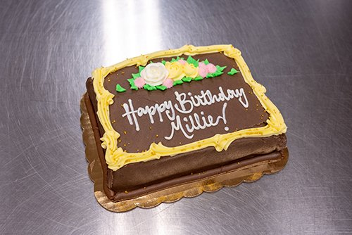 a freshly baked cake that is hand frosted and decorated for a birthday