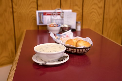 a bowl of Wild Rice Soup with a basketball of fresh rolls