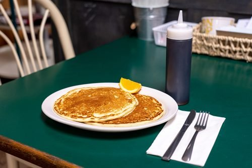 a plate of fluffy tasty looking pancakes on a green table at raphael's bakery next to a bottle of syrup